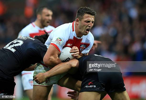 Sam Burgess of England is tackled by Tohu Harris and Martin Taupau of New Zealand during the Four Nations match between England and New Zealand Kiwis...