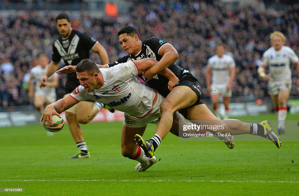<a gi-track='captionPersonalityLinkClicked' href=/galleries/search?phrase=Sam+Burgess&family=editorial&specificpeople=2650353 ng-click='$event.stopPropagation()'>Sam Burgess</a> of England scores their third try as Roger Tuivasa-Scheck of New Zealand tries to stop him during the Rugby League World Cup Semi Final match between New Zealand and England at Wembley Stadium on November 23, 2013 in London, England.