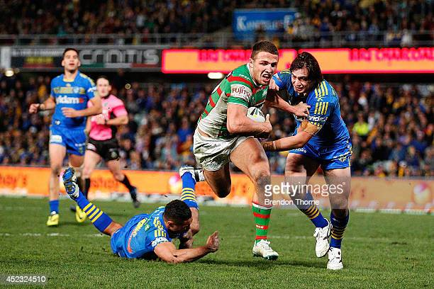 Sam Burgess of the Rabbitohs fends off Tepai Moeroa of the Eels to score a try during the round 19 NRL match between the Parramatta Eels and the...