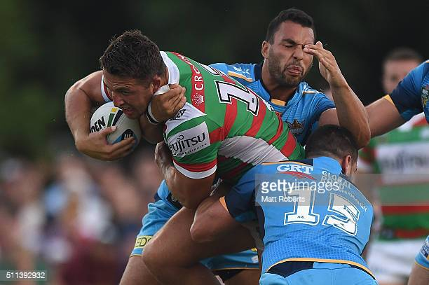 Sam Burgess of the Rabbitohs is tackled by Lachlan Burr and Ryan James of the Titans during the NRL trial match between the Gold Coast Titans and the...