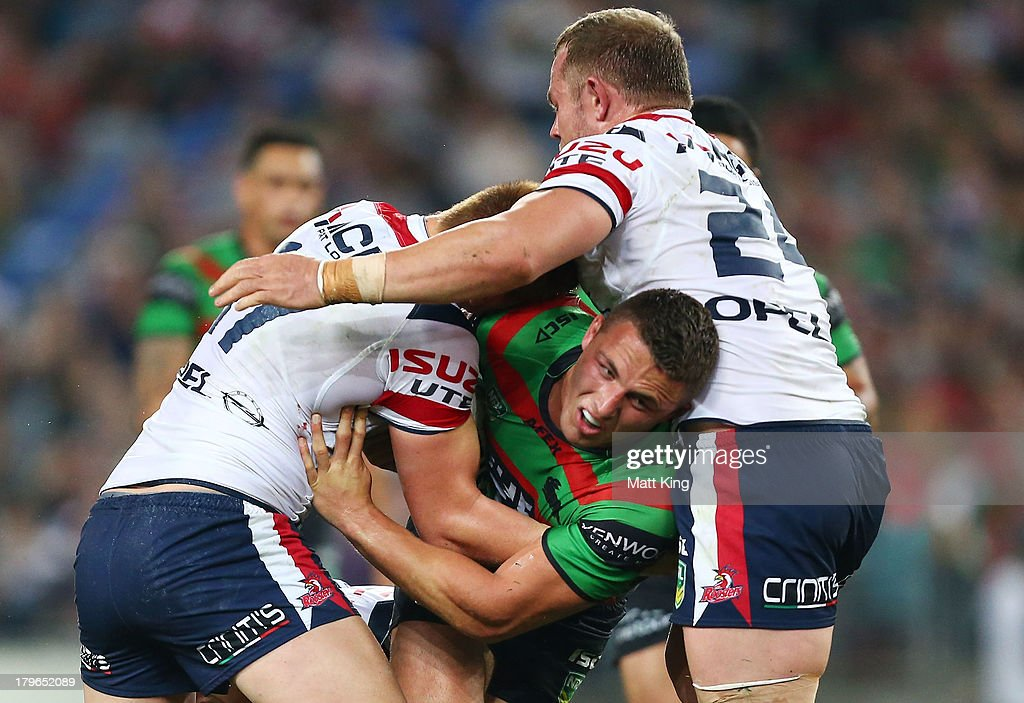 Sam Burgess of the Rabbitohs is tackled during the round 26 NRL match between the South Sydney Rabbitohs and the Sydney Roosters at ANZ Stadium on September 6, 2013 in Sydney, Australia.