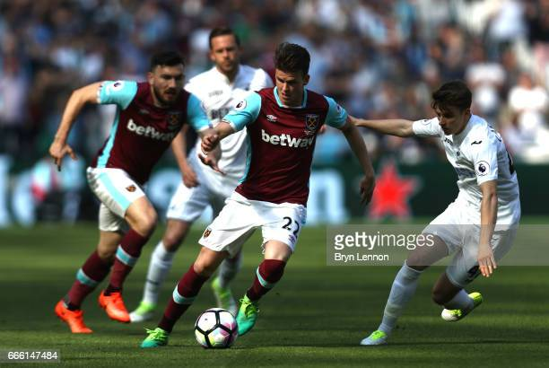 Sam Byram of West Ham United attempts to take the ball past Tom Carroll of Swansea City during the Premier League match between West Ham United and...