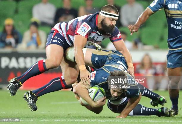 Sam Carter of the Brumbies is tackled by James Hanson of the Rebels during the round eight Super Rugby match between the Rebels and the Brumbies at...