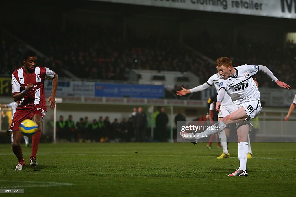 Sam Clucas (R) of Hereford United shoots as Sido Jombati (L) of Cheltenham Town looks on during the FA Cup with Budweiser Second Round Replay match between Hereford United and Cheltenham Town at Edgar Street Athletic Ground on December 11, 2012 in Hereford, England.