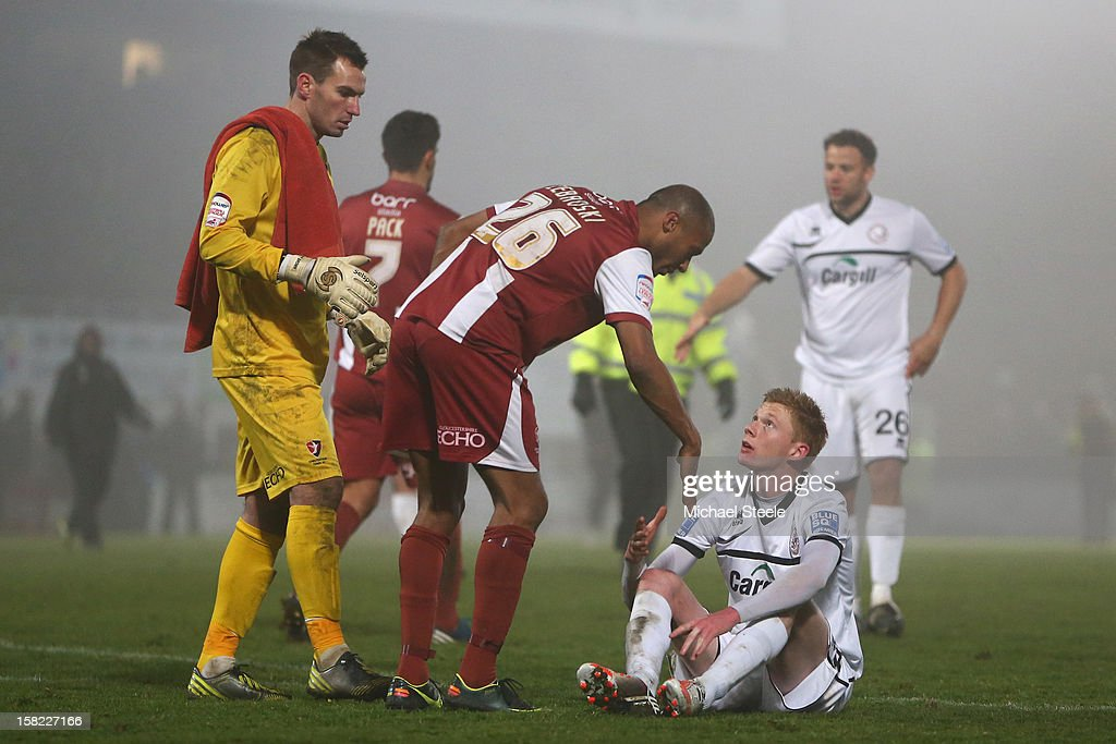 Sam Clucas (R) of Hereford United sits dejected on the final whistle after his sides 1-2 defeat as Chris Zebroski (C) and Scott Brown (L) of Cheltenham Town approach to shake hands during the FA Cup with Budweiser Second Round Replay match between Hereford United and Cheltenham Town at Edgar Street Athletic Ground on December 11, 2012 in Hereford, England.