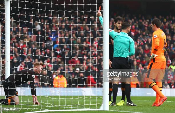 Sam Clucas of Hull City is shown a red card by referee Mark Clattenburg because of a hand ball during the Premier League match between Arsenal and...