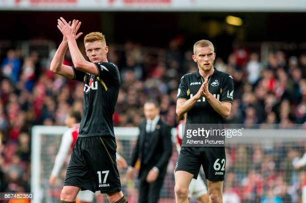 Sam Clucas of Swansea City and Oliver McBurnie applaud fans during the Premier League match between Arsenal and Swansea City at Emirates stadium on...