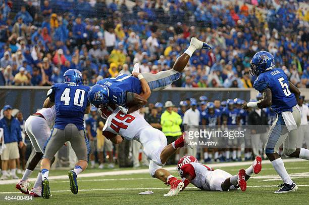 Sam Craft of the Memphis Tigers dives over Adam Noble of the Austin Peay Governors on August 30 2014 at Liberty Bowl Memorial Stadium in Memphis...