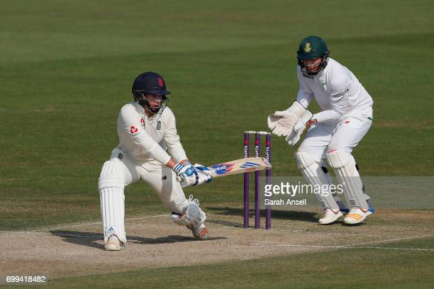 Sam Curran of the England Lions sweeps as South Africa A wicket keeper Heinrich Klaasen looks on during day 1 of the match between England Lions and...