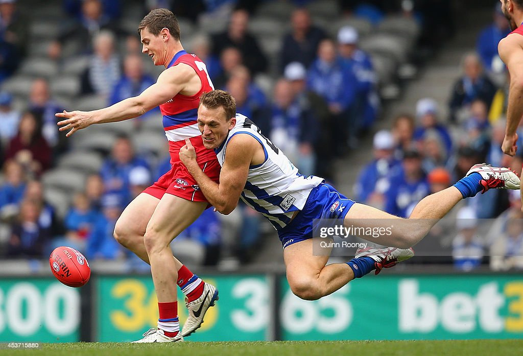 Sam Darley of the Bulldogs kicks whilst being tackled by Drew Petrie of the Kangaroos during the round 21 AFL match between the North Melbourne...