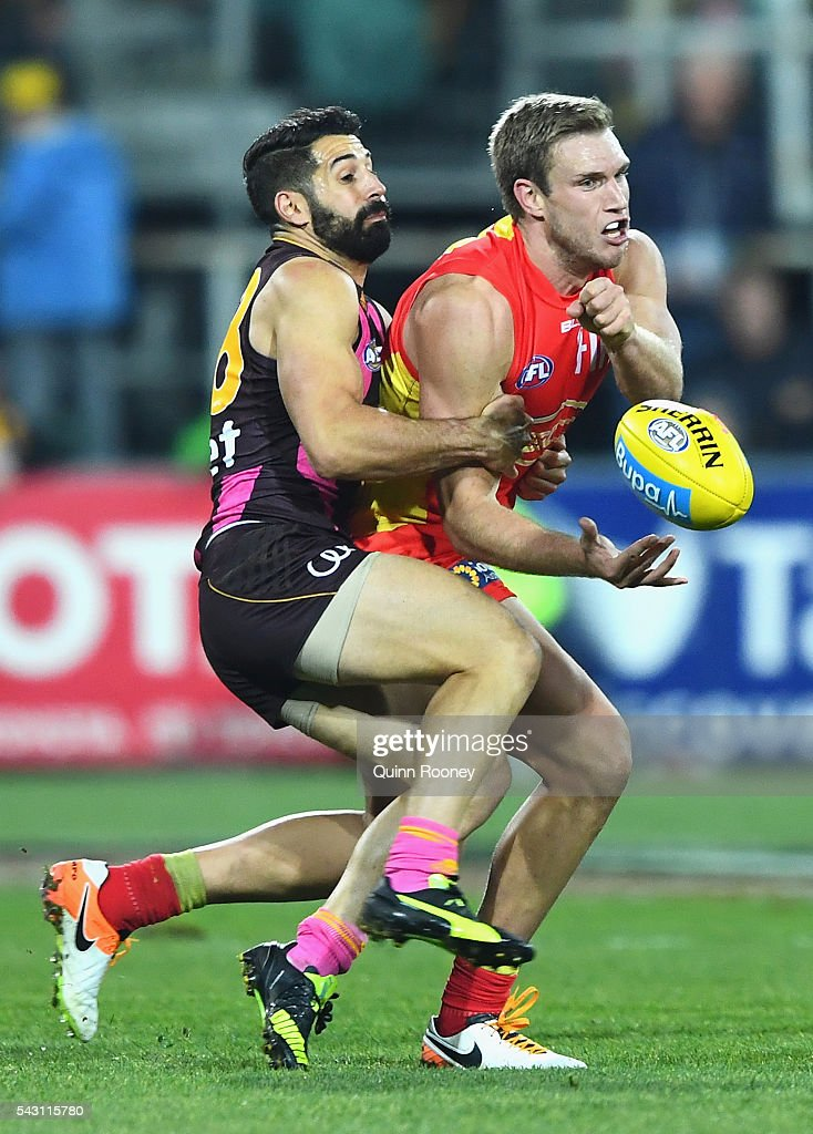 Sam Day of the Suns handballs whilst being tackled by Paul Puopolo of the Hawks during the round 14 AFL match between the Hawthorn Hawks and the Gold Coast Suns at Aurora Stadium on June 26, 2016 in Launceston, Australia.