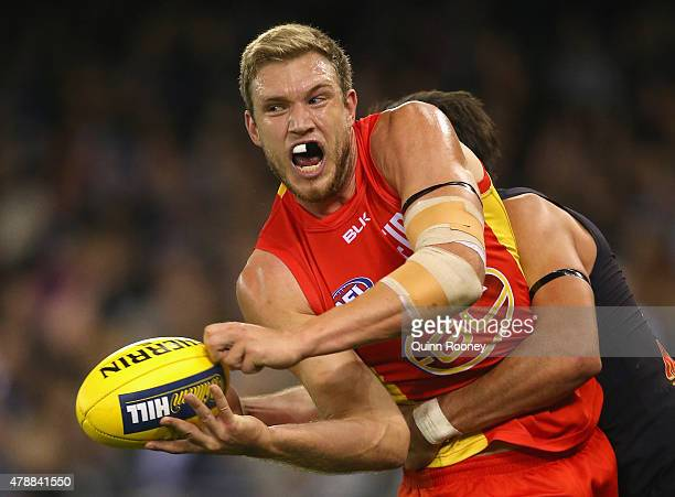 Sam Day of the Suns handballs whilst being tackled by Troy Menzel of the Blues during the round 13 AFL match between the Carlton Blues and the Gold...
