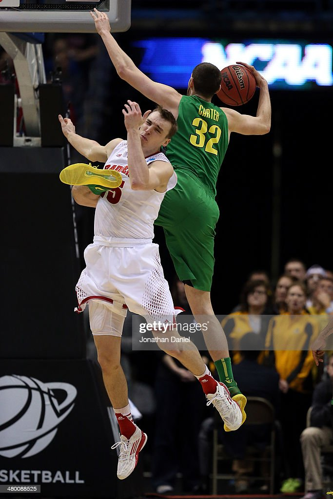 Sam Dekker of the Wisconsin Badgers gets hit in the face by Ben Carter of the Oregon Ducks in the first half during the third round of the 2014 NCAA...