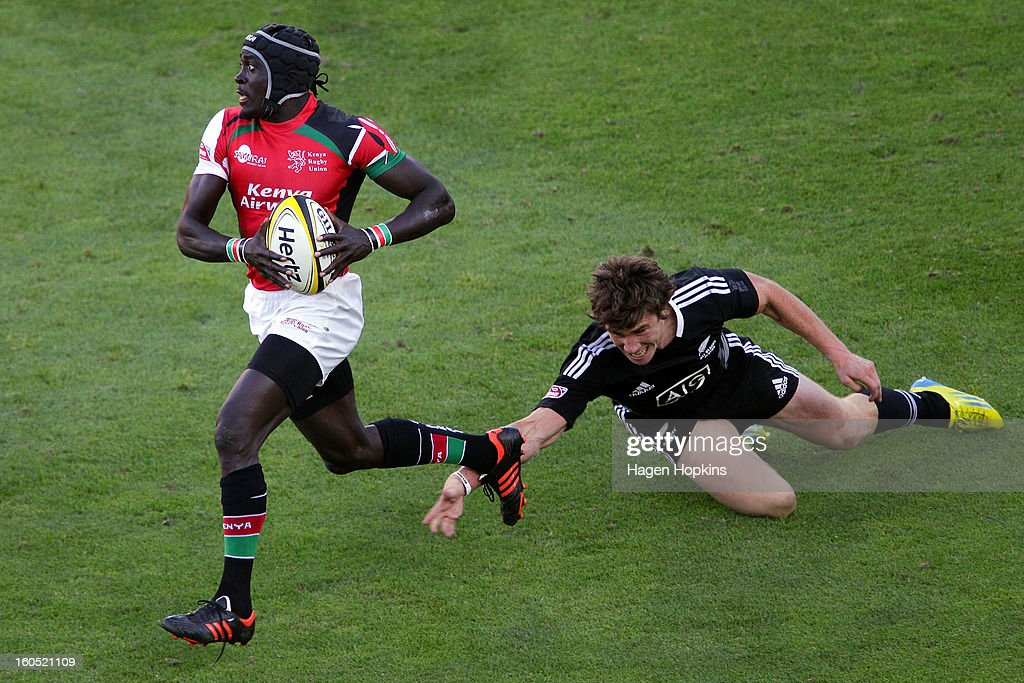 Sam Dickson of New Zealand ankle-taps Collins Injera of Kenya of the All Blacks Sevens in the semifinal cup match between New Zealand and Kenya during the 2013 Wellington Sevens at Westpac Stadium on February 2, 2013 in Wellington, New Zealand.