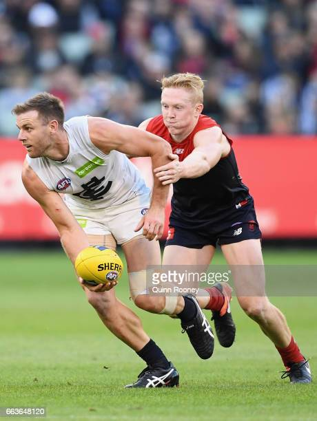 Sam Docherty of the Blues handballs whilst being tackled by Clayton Oliver of the Demons during the round two AFL match between the Melbourne Demons...