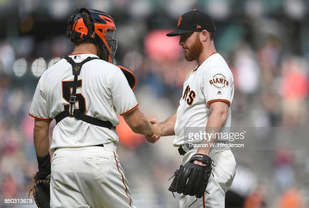 Sam Dyson and Nick Hundley of the San Francisco Giants shake hands after they defeated the Colorado Rockies 40 at ATT Park on September 20 2017 in...