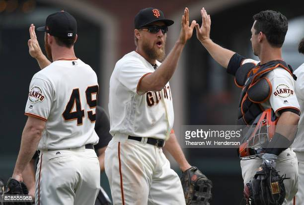 Sam Dyson Hunter Pence and Buster Posey of the San Francisco Giants celebrates defeating the Chicago Cubs 31 at ATT Park on August 9 2017 in San...