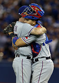 Sam Dyson of the Texas Rangers celebrates with his teammate Robinson Chirinos after defeating the Toronto Blue Jays after game one of the American...