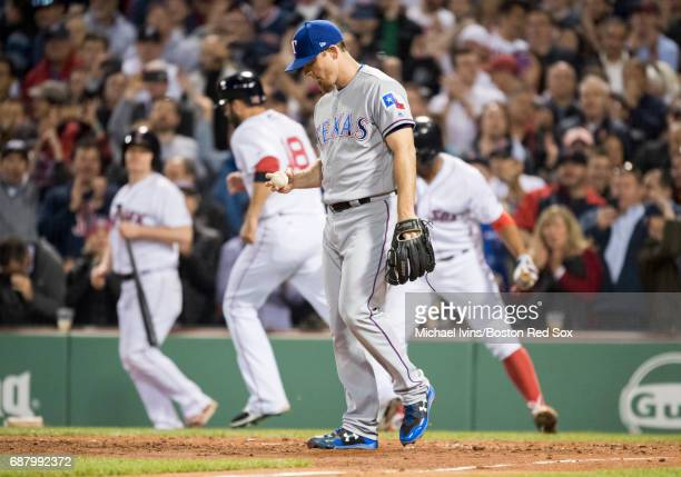 Sam Dyson of theTexas Rangers reacts after throwing a wild pitch allowing a run to score against the Boston Red Sox in the seventh inning at Fenway...