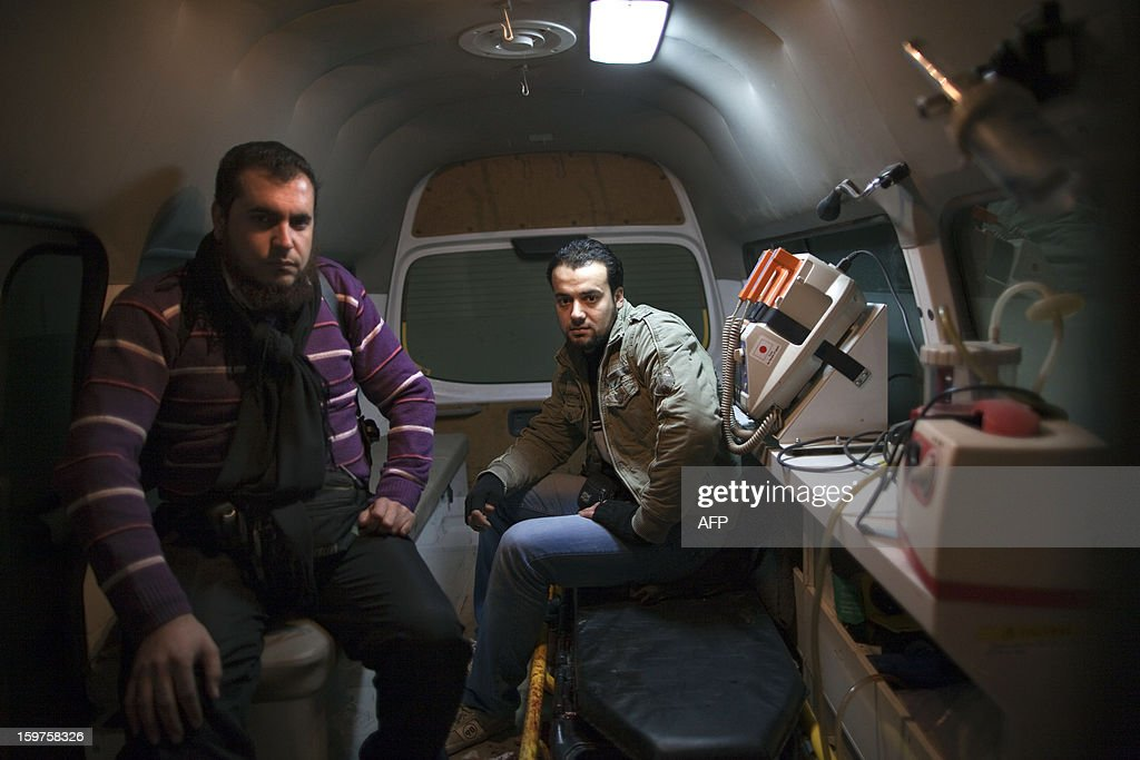 Sam Eddin, 32, coordinator of an amublance service, sits next to driver Abu Bakr inside an ambulance stationed at their headquarters in the war-torn northern Syrian city of Aleppo on January 12, 2013. 'We work 24 hours seven days a week. The war never stops and we don't either,' Abu Bakr says. AFP PHOTO/JM LOPEZ