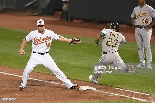 Sam Fuld of the Oakland Athletics can't beat the throw to Chris Davis of the Baltimore Orioles in the fifth inning on a bunt during a baseball game...