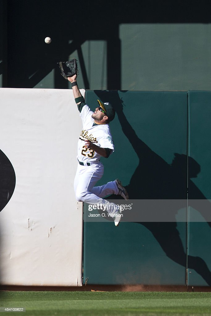 <a gi-track='captionPersonalityLinkClicked' href=/galleries/search?phrase=Sam+Fuld&family=editorial&specificpeople=4505687 ng-click='$event.stopPropagation()'>Sam Fuld</a> #23 of the Oakland Athletics leaps for but is unable to catch a fly ball hit of the bat of Erick Aybar (not pictured) of the Los Angeles Angels of Anaheim for a two run double during the second inning at O.co Coliseum on August 24, 2014 in Oakland, California.