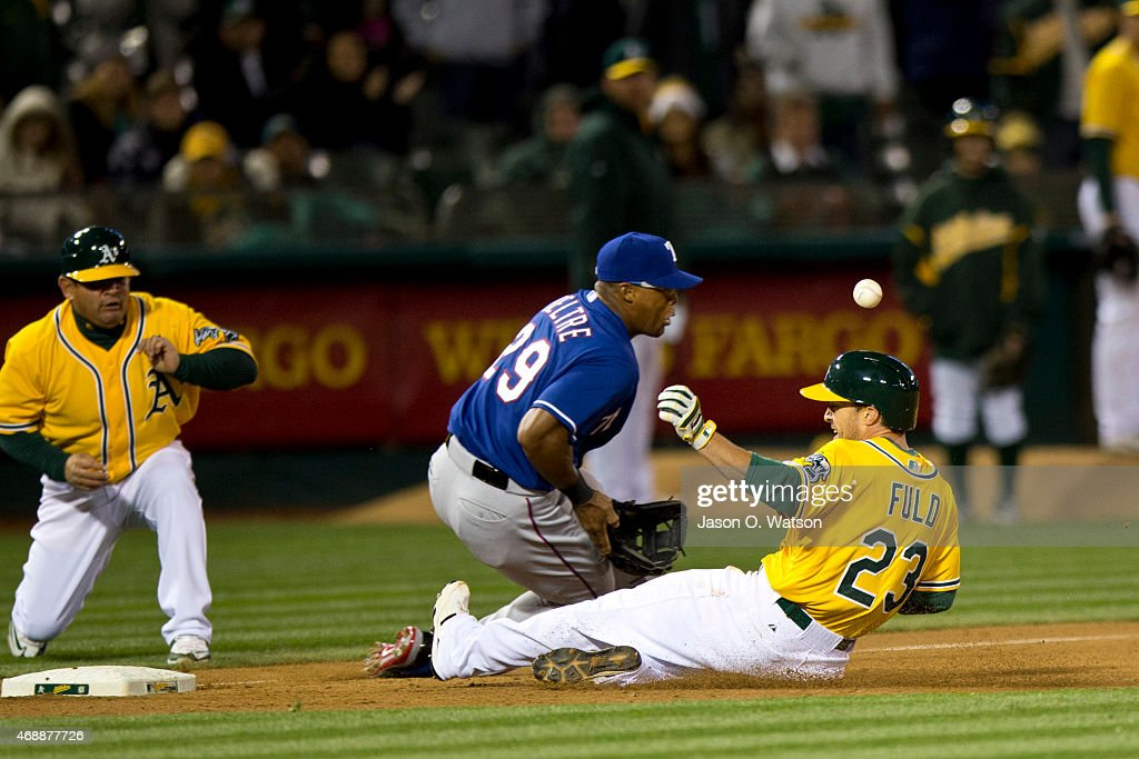 <a gi-track='captionPersonalityLinkClicked' href=/galleries/search?phrase=Sam+Fuld&family=editorial&specificpeople=4505687 ng-click='$event.stopPropagation()'>Sam Fuld</a> #23 of the Oakland Athletics slides into third base for a triple past <a gi-track='captionPersonalityLinkClicked' href=/galleries/search?phrase=Adrian+Beltre&family=editorial&specificpeople=202631 ng-click='$event.stopPropagation()'>Adrian Beltre</a> #29 of the Texas Rangers during the sixth inning at O.co Coliseum on April 7, 2015 in Oakland, California.