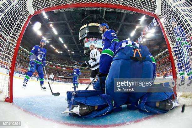 Sam Gagner and Alexander Edler of the Vancouver Canucks and Kyle Clifford of the Los Angeles Kings look on as they puck gets behind Anders Nilsson of...