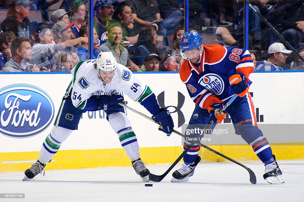 <a gi-track='captionPersonalityLinkClicked' href=/galleries/search?phrase=Sam+Gagner&family=editorial&specificpeople=4042961 ng-click='$event.stopPropagation()'>Sam Gagner</a> #89 of the Edmonton Oilers battles for the puck against Kellan Lain #54 of the Vancouver Canucks during a preseason NHL game at Rexall Place on September 21, 2013 in Edmonton, Alberta, Canada.
