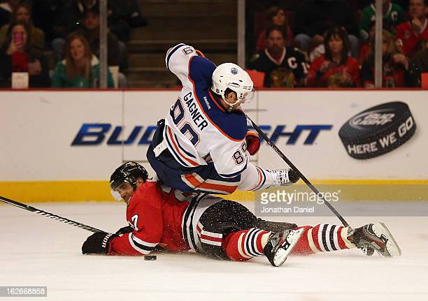 Sam Gagner of the Edmonton Oilers falls over Johnny Oduya of the Chicago Blackhawks at the United Center on February 25 2013 in Chicago Illinois
