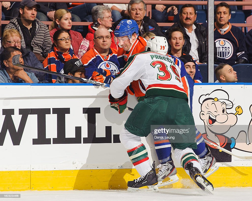 Sam Gagner #89 of the Edmonton Oilers gets flattened against the boards by Nate Prosser #39 of the Minnesota Wild during an NHL game at Rexall Place on February 21, 2013 in Edmonton, Alberta, Canada.