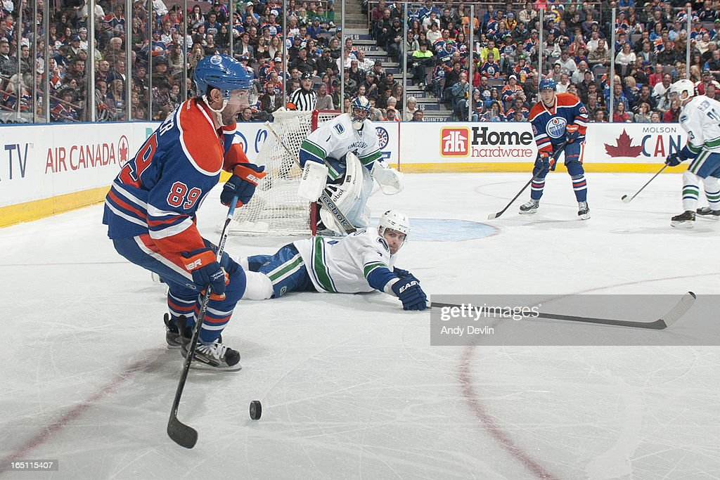 <a gi-track='captionPersonalityLinkClicked' href=/galleries/search?phrase=Sam+Gagner&family=editorial&specificpeople=4042961 ng-click='$event.stopPropagation()'>Sam Gagner</a> #89 of the Edmonton Oilers handles the puck as <a gi-track='captionPersonalityLinkClicked' href=/galleries/search?phrase=Dan+Hamhuis&family=editorial&specificpeople=204213 ng-click='$event.stopPropagation()'>Dan Hamhuis</a> #2 of the Vancouver Canucks goes down to block the pass on March 30, 2013 at Rexall Place in Edmonton, Alberta, Canada.