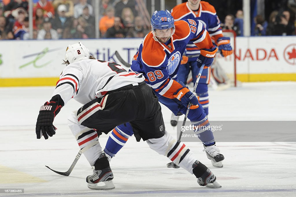 Sam Gagner #89 of the Edmonton Oilers passes the puck between the legs of Duncan Keith #2 of the Chicago Blackhawks on April 24, 2013 at Rexall Place in Edmonton, Alberta, Canada.