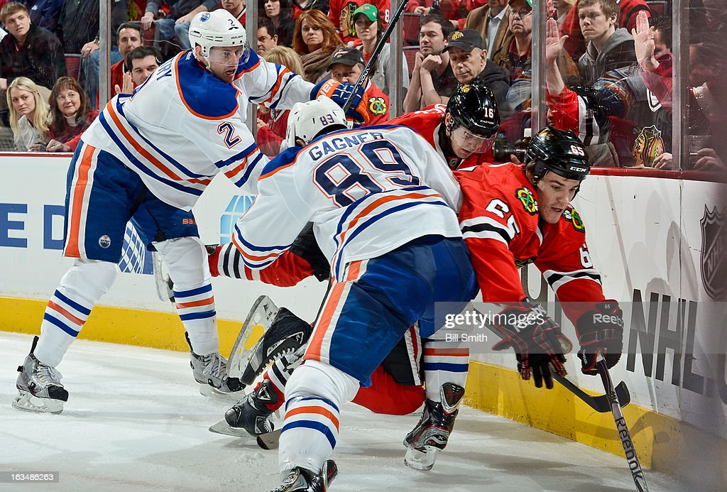 <a gi-track='captionPersonalityLinkClicked' href=/galleries/search?phrase=Sam+Gagner&family=editorial&specificpeople=4042961 ng-click='$event.stopPropagation()'>Sam Gagner</a> #89 of the Edmonton Oilers pushes into Andrew Shaw #65 of the Chicago Blackhawks, as Jeff Petry #2 of the Oilers and Marcus Kruger #16 of the Blackhawks skate behind, during the NHL game on March 10, 2013 at the United Center in Chicago, Illinois.