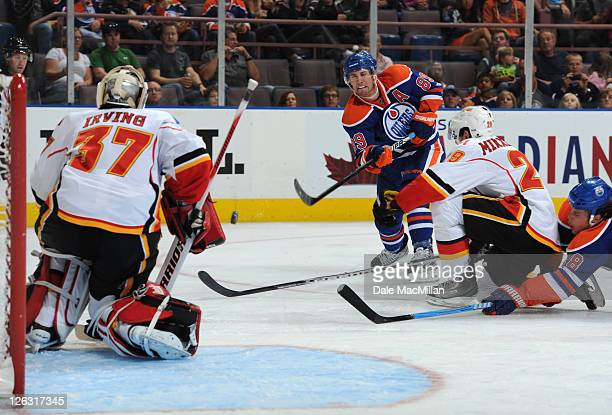 Sam Gagner of the Edmonton Oilers shoots the puck on Leland Irving of the Calgary Flames as teammate Brendan Mikkelson tries to block it during...