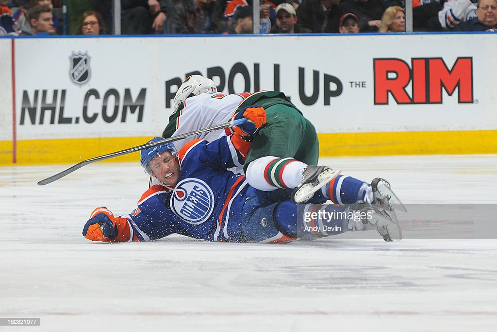Sam Gagner #89 of the Edmonton Oilers skates gets tangled up with a player of the Minnesota Wild on February 21, 2013 at Rexall Place in Edmonton, Alberta, Canada.