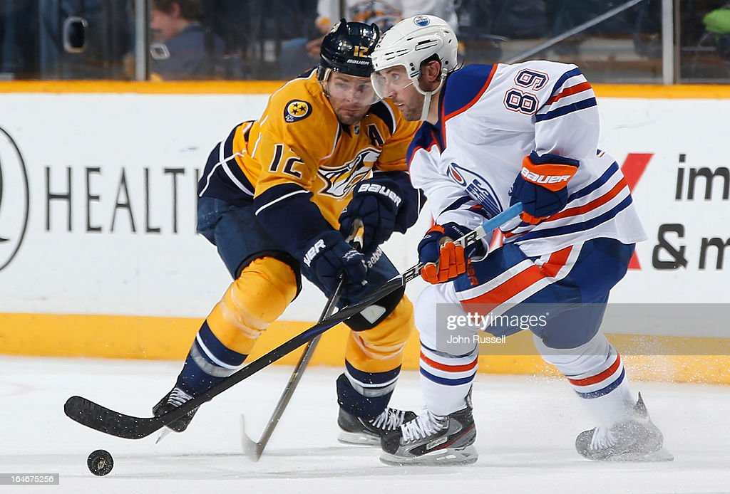 <a gi-track='captionPersonalityLinkClicked' href=/galleries/search?phrase=Sam+Gagner&family=editorial&specificpeople=4042961 ng-click='$event.stopPropagation()'>Sam Gagner</a> #89 of the Edmonton Oilers skates the puck in the zone against <a gi-track='captionPersonalityLinkClicked' href=/galleries/search?phrase=Mike+Fisher+-+Ice+Hockey+Player&family=editorial&specificpeople=204732 ng-click='$event.stopPropagation()'>Mike Fisher</a> #12 of the Nashville Predators during an NHL game at the Bridgestone Arena on March 25, 2013 in Nashville, Tennessee.