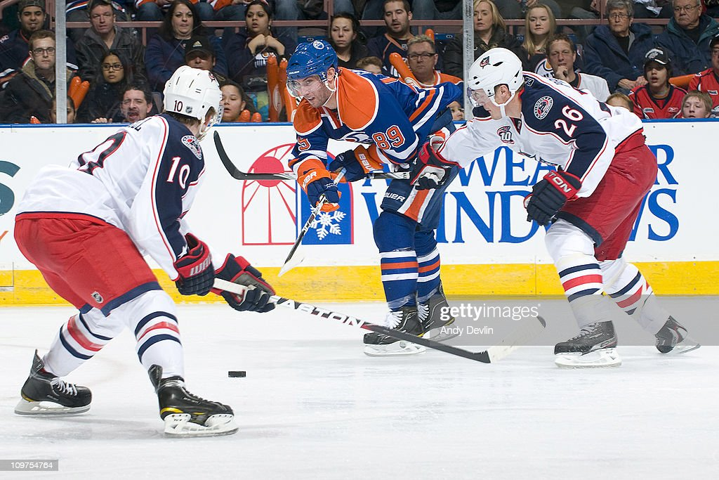 Sam Gagner #89 of the Edmonton Oilers tries to put a pass between Kris Russell #10 and Samuel Pahlsson #26 of the Columbus Blue Jackets at Rexall Place on March 3, 2011 in Edmonton, Alberta, Canada.