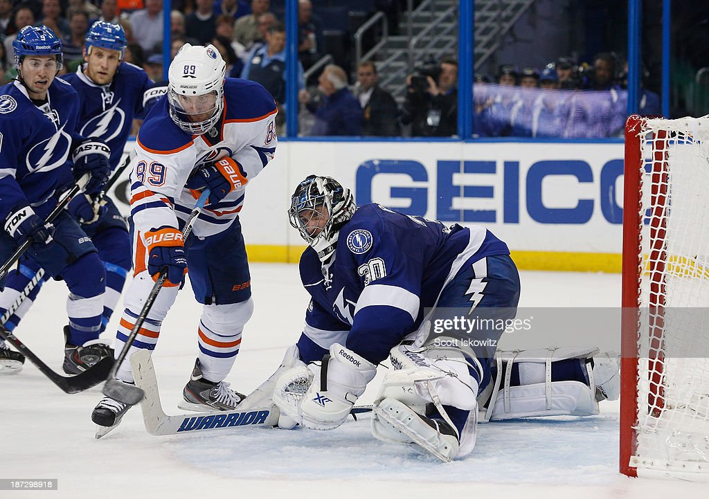 <a gi-track='captionPersonalityLinkClicked' href=/galleries/search?phrase=Sam+Gagner&family=editorial&specificpeople=4042961 ng-click='$event.stopPropagation()'>Sam Gagner</a> #89 of the Edmonton Oilers tries to shoot the puck against <a gi-track='captionPersonalityLinkClicked' href=/galleries/search?phrase=Ben+Bishop&family=editorial&specificpeople=700137 ng-click='$event.stopPropagation()'>Ben Bishop</a> #30 of the Tampa Bay Lightning during the third period at Tampa Bay Times Forum on November 7, 2013 in Tampa, Florida.