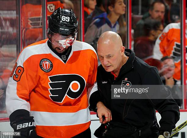 Sam Gagner of the Philadelphia Flyers is helped off the ice after he cut his head in the first period against the Carolina Hurricanes on November 23...