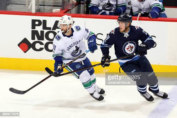 Sam Gagner of the Vancouver Canucks and Patrik Laine of the Winnipeg Jets keep an eye on the play during third period action at the Bell MTS Place on...