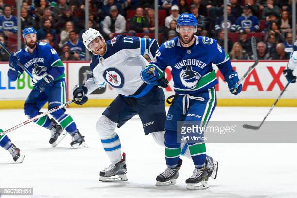 Sam Gagner of the Vancouver Canucks checks Adam Lowry of the Winnipeg Jets during their NHL game at Rogers Arena October 12 2017 in Vancouver British...