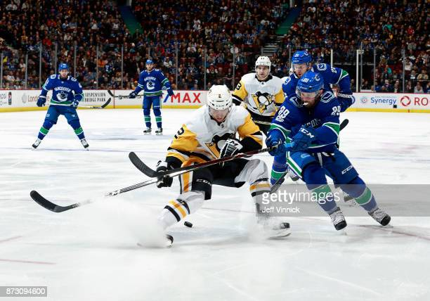 Sam Gagner of the Vancouver Canucks checks Chad Ruhwedel of the Pittsburgh Penguins during their NHL game at Rogers Arena November 4 2017 in...