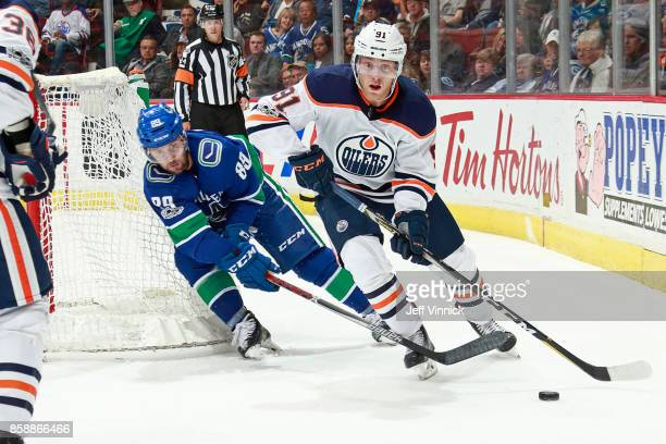 Sam Gagner of the Vancouver Canucks checks Drake Caggiula of the Edmonton Oilers during their NHL game at Rogers Arena October 7 2017 in Vancouver...
