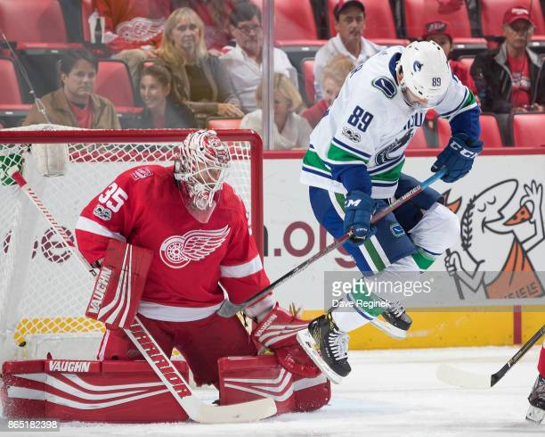 Sam Gagner of the Vancouver Canucks jumps out of the way of a shot in front of goaltender Jimmy Howard of the Detroit Red Wings during an NHL game at...