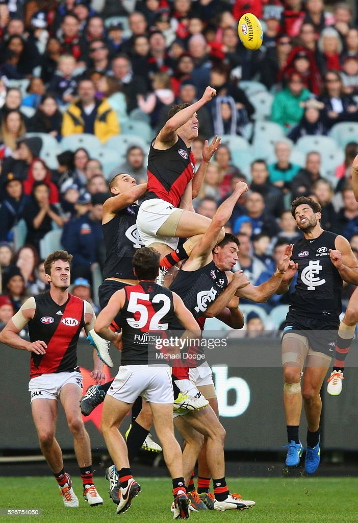 Sam Grimley of the Bombers punches the ball away over Matthew Kreuzer of the Blues during the round six AFL match between the Carlton Blues and the Essendon Bombers at Melbourne Cricket Ground on May 1, 2016 in Melbourne, Australia.