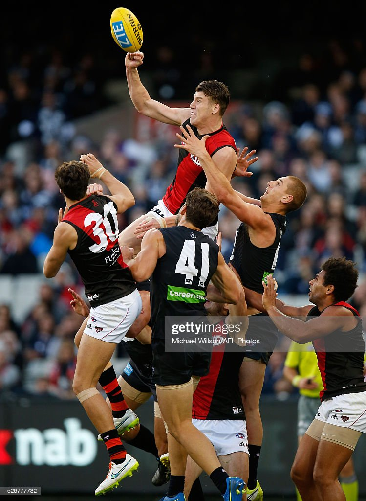 Sam Grimley of the Bombers punches the ball from Levi Casboult (left) and Liam Jones of the Blues during the 2016 AFL Round 06 match between the Carlton Blues and the Essendon Bombers at the Melbourne Cricket Ground, Melbourne on May 1, 2016.
