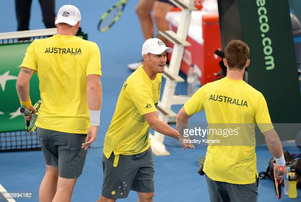Sam Groth and John Peers of Australia celebrate winning the first set with Team Captain Lleyton Hewitt in their doubles match against Steve Johnson...