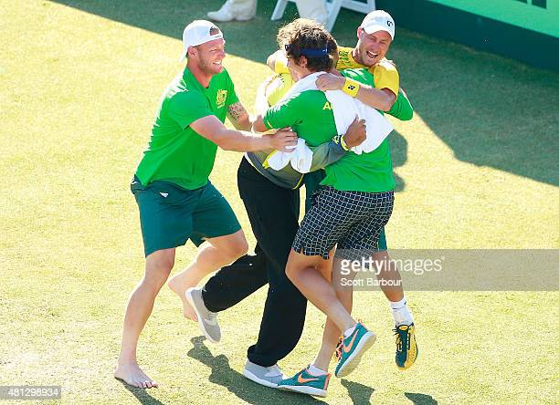 Sam Groth Thanasi Kokkinakis and Nick Kyrgios run on court to congratulate teammate Lleyton Hewitt of Australia as he celebrates winning the reverse...