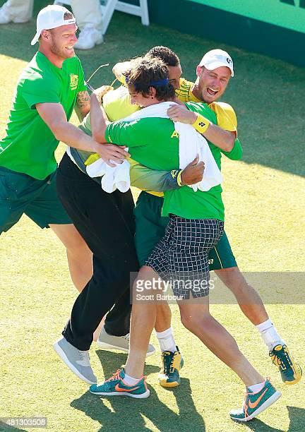Sam Groth Thanasi Kokkinakis and Nick Kyrgios run on court to congratulate teammate Lleyton Hewitt of Australia as he celebrates winning the reverse...